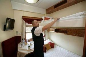 Проводник заправляет постель в вагоне повышенной комфортности